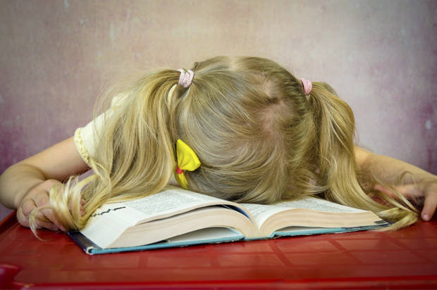 blond girl sleeping over open book