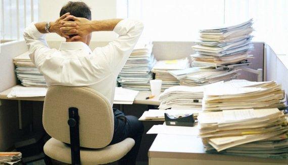 employe avec plein de dossiers sur son bureau